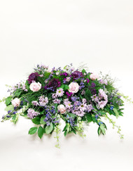 A beautiful mix of purple roses, daisies and other accent flowers for an elegant tribute casket piece.