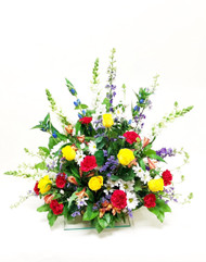 A beautiful mix of yellow red and white fresh flowers designed in a bright sympathy tribute.