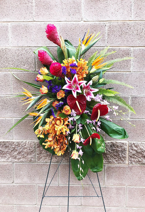 This Beautiful Sympathy Tribute is designed with a bright mix of tropical plants and flowers. Bright colors make a statement in this memorial tribute.