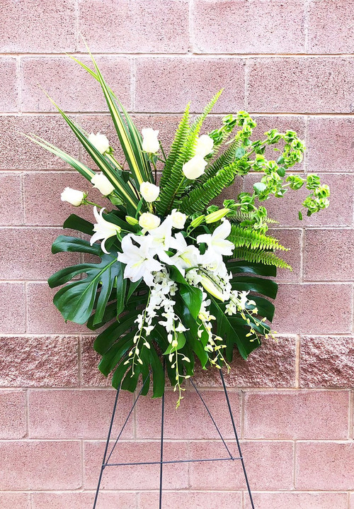 Make a statement with this unique tropical standing spray. This sympathy spray is designed with whites and greens. Fresh white roses and locally grown lilies contrasted with beautiful and bold greens.
