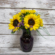 Beautiful sunflowers arranged in a bold  vase.  We add a touch of purple filler making these locally grown sunflowers stand out!
