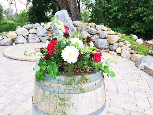 Just what a wine barrel needs, late summer mix of white and red gerberas, white snapdragons, fun interesting fillers and greens with burgundy dianthus accents.