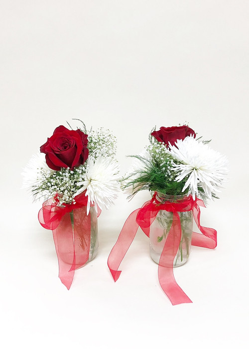 Simple red and white Mason jar table decor. Bold red and white fresh flowers with ribbon accents