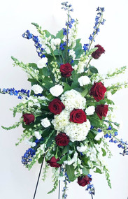 Standing Spray designed with a variety of fresh flowers in red white and blue.