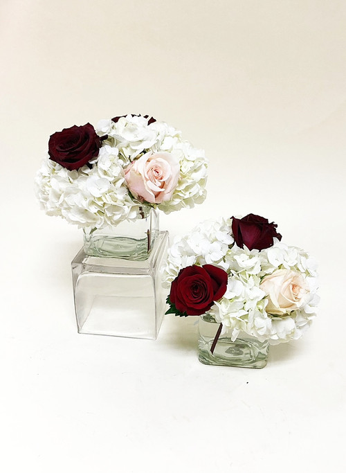 Simple glass cubes of hydrangea, burgundy and blush roses make for an elegant touch for your table centerpieces.