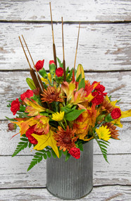 A Mix of fall fresh flowers designed in a fall tin!