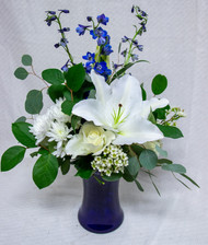 Inspired by our favorite Disney movie - Frozen, this arrangement has the approval of the ice queen herself. An arrangement made in a bold cobalt blue vase and big white stargazer lilies, roses, and other white and blue accent flowers, this arrangement is Elsa's favorite arrangement to send!