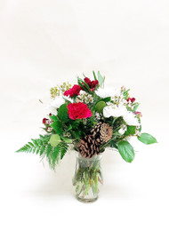 A small winter mixed arrangement of white snowflake poms, red carnations and other seasonal flowers accented with some pinecones for an extra winter touch!