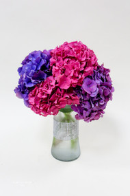 A mixture of pink and dark blue or purple hydrangeas in a clear fluted vase. This arrangement is a stunner!