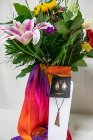 Start with fun, bright seasonal flowers arranged in a vase. Then, accent it with a hand designed silk scarf from a local artist - Silk Sensations AND a necklace and earring set from the local jewelry designers at DC designs!