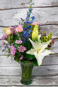 This beautiful fresh flower arrangement includes locally grown Stargazer Lilies and bright blue Delphinium as the vibrant focal flowers to make a bold statement. This arrangement also includes other seasonal fresh flowers to accent the blue and pink, designed in a clear glass vase with mixed greenery for a great texture.