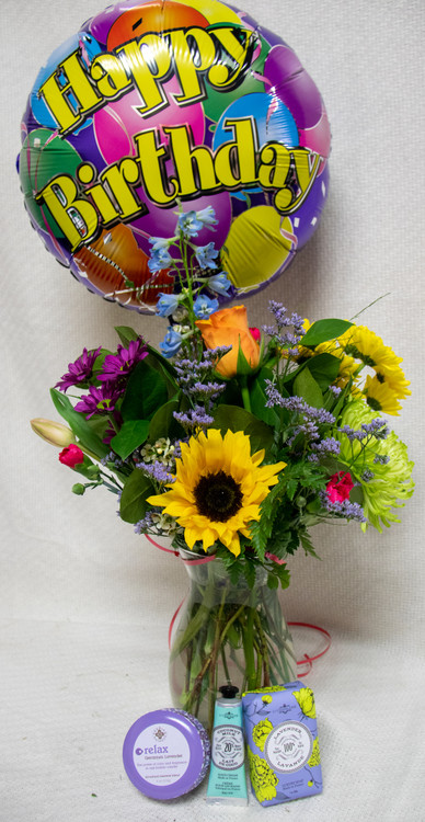 Send a bundle full of festive flowers and gifts for any occasion! This bundle features a Designer's choice Arrangement, moisturizing floral soap and lotion, balloon, and a candle!