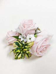 Soft pastel pink roses and a touch of greens make this simple corsage pop!