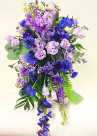 a colorful cascading bouquet perfect for your mountain wedding!  In pinks, blues and purples, including lisianthus, delphinium,  cornflowers, stock and fun variety of  interesting greens complete this wildflower Colorado look.