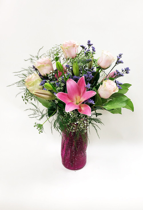 This vase arrangement includes locally grown Stargazer lilies, beautiful pink premium roses, mixed fillers and a pink colored vase. A beautiful and fresh and fragrant display of two popular long lasting flowers.