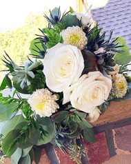 This gorgeous free style bouquet is designed with succulents, white roses, white mums, mixed greens, thistle, and eucalyptus! An amazing mix of soft whites and all greens!