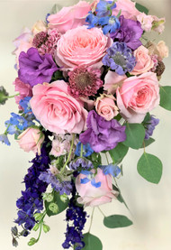 A beautiful cascading bouquet of Pink Roses, Lisianthis, larkspur and mixed flowers make up this colorful bridal bouquet!