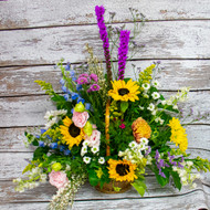 A mix of fresh cut wild flowers in a woven basket with a mix of vibrant colors and a variety of colors. You will find sunflowers, larkspur, delphinium, daisies and other accent flowers in this loving tribute.