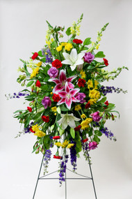 Premium Gardeners Tribute Sympathy arrangement with a mix of vibrant bold colors and fresh cut local grown Lilies. Accented by a variety of mixed fresh cut flowers in a variety of colors. May include Alstromeria, premium fresh cut long stemmed roses and carnations of select colors.