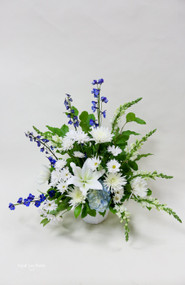 White locally grown fresh cut lilies arranged with blue delphinium and other white seasonal fresh-cut flowers.