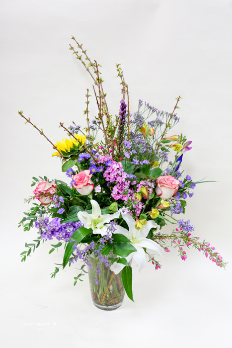 A Beautiful unique fresh flower arrangement designed by your local Loveland Florist. Mixture of Stargazer Lilies, Roses and blooming branches.