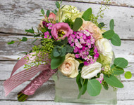 This gorgeous bouquet is designed with pastel roses with pops of purple and set with greenery.