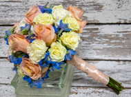 This stunning boho bouquet is filled with white and peach roses with pops of blue wrapped with a satin ribbon.