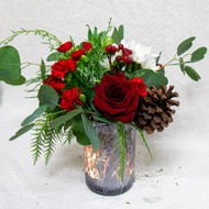 A red rose surrounded by assorted seasonal flowers, winter greens and a pinecone will capture that festive mood!   In a holiday glass vase.