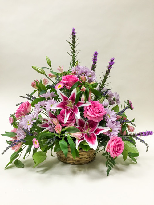 A premium peaceful gaze of locally grown stargazer lilies, beautiful premium garden roses, and accented by purple hues of mixed fresh-cut flowers and other fillers.