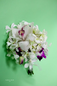 A touch of tropical splendor!  Mix of orchids in  white, ivory and a hint of fuschia!