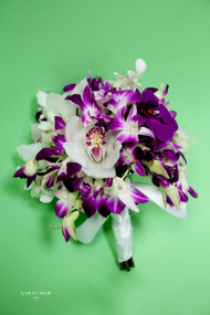 Mixed orchids make up this interesting tropical handtied.