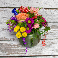 A bright and fun mixture of flowers in a glass bowl with painted candles. a great way to celebrate someone's birthday