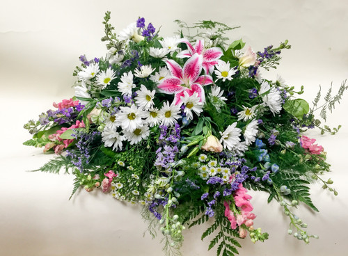 Premium Pink tribute Casket Spray  accented with Local Grown Lilies and White Daisies. Made with love by the Girls at Earle's.