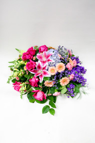 A Vibrant Garden Casket Spray made with Local Grown Lilies and Colored Roses with green fillers and other mixed fresh flowers, brought to you by the Girls at Earle's.