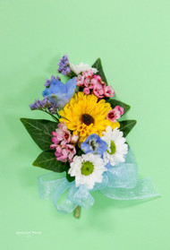 Fresh summer mix corsage of viking poms, delphinium,  micro daisies and waxflower.