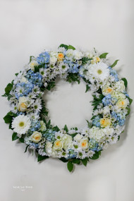 A wreath hanging on an easel with blue hydrangea, white daisies, pale yellow roses and white gerbera daisies.