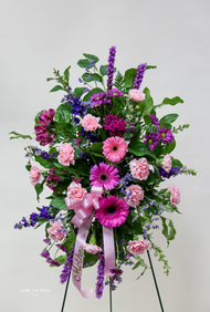 A standing easel spray of shades of pink flowers including carnations, gerberas and snapdragons -   beautifully feminine.