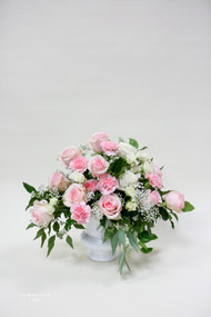 A clustered contemporary combination of pink roses for a different look and feel for home or service.