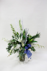 A vase arrangement with lilies, greenery, and silver accents
