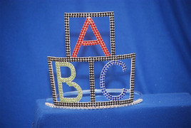 "A ""Premier Crowns"" design. Alphabet blocks tiara with adjustable band. 6"" tall"