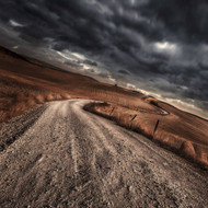 A Country Road In Field With Stormy Sky Above Tuscany Italy