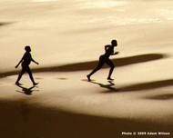 Lesotho Desert Scene  Silhouetted by the sun, runners cross the Lesotho dunes  Photo © 2009 Adam Wilson; The International Calendar Project