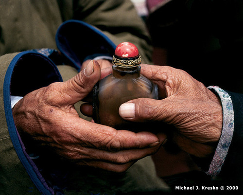 Zoolan, Khövsgöl Province, Mongolia  In a ritual greeting between two Mongolian elders, the bearer of this snuff bottle offers it with his right hand, while the left is cupped under his elbow. Passing objects in this way is a sign of respect, holiness, and purity.  Photo © 2000 Michael J. Kresko; featured in the 2001 International Calendar