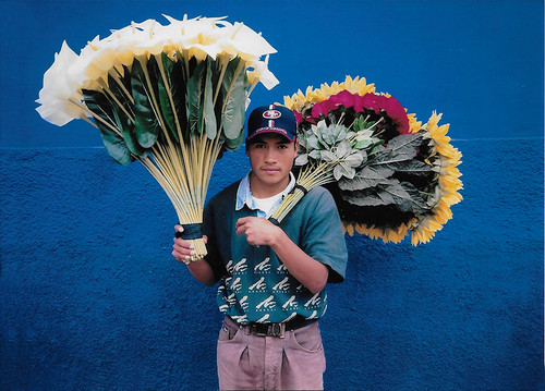 Mexico Flower seller.  Contemporary street vendors in Mexico—especially the boys—often sport Western clothing and baseball caps. These flower sellers, with their oversized floral bundles, can sometimes be seen near brightly painted stucco walls, making for vibrant photographic portraits.  Photo © 1999 Zane Williams; The International Calendar Project