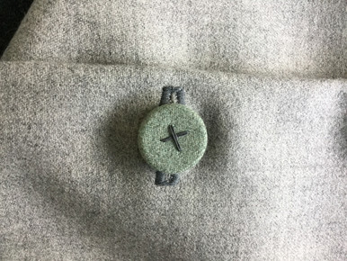 Detail of the Seafoam fabric covered & hand stitched button on the neutral marled wool textile.