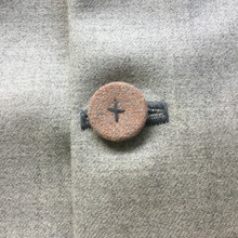 Detail of fabric covered button which is hand stitched in mid-grey yarn. Peachy on neutral marled wool. 50x50cm.