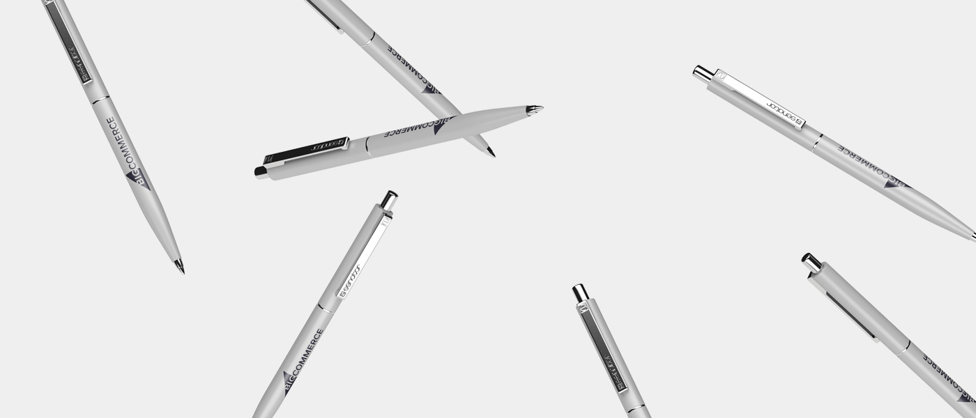 Customized pens with BigCommerce logo, flying through the air.