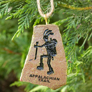 "This natural-looking ornament depicts a petroglyph or Kokopelli hiker and ""Appalachian Trail"" underneath."