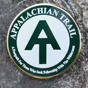 "A.T. monogram pin ringed with ""A footpath for those who seek fellowship with the wilderness."""