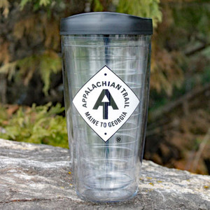 Thermal insulated, clear tumbler with lid, bearing the A.T. diamond logo in white.